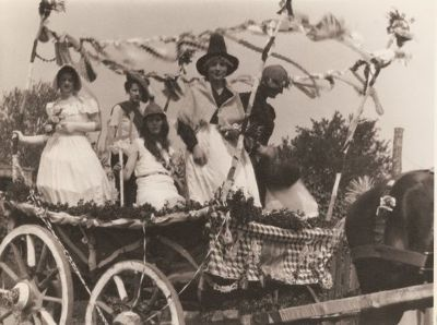 historical image of people in fancy dress on horse drawn cart
