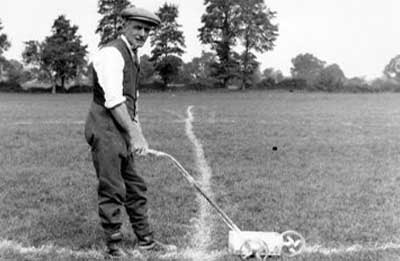 historical image of man whitelining old playing field for football